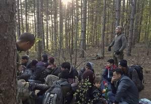 Detenção ilegal. Membros do grupo de vigilantes Organização para a Proteção de Cidadãos Búlgaros conduzem refugiados afegãos detidos na fronteira da Bulgária com a Turquia Foto: - / AFP