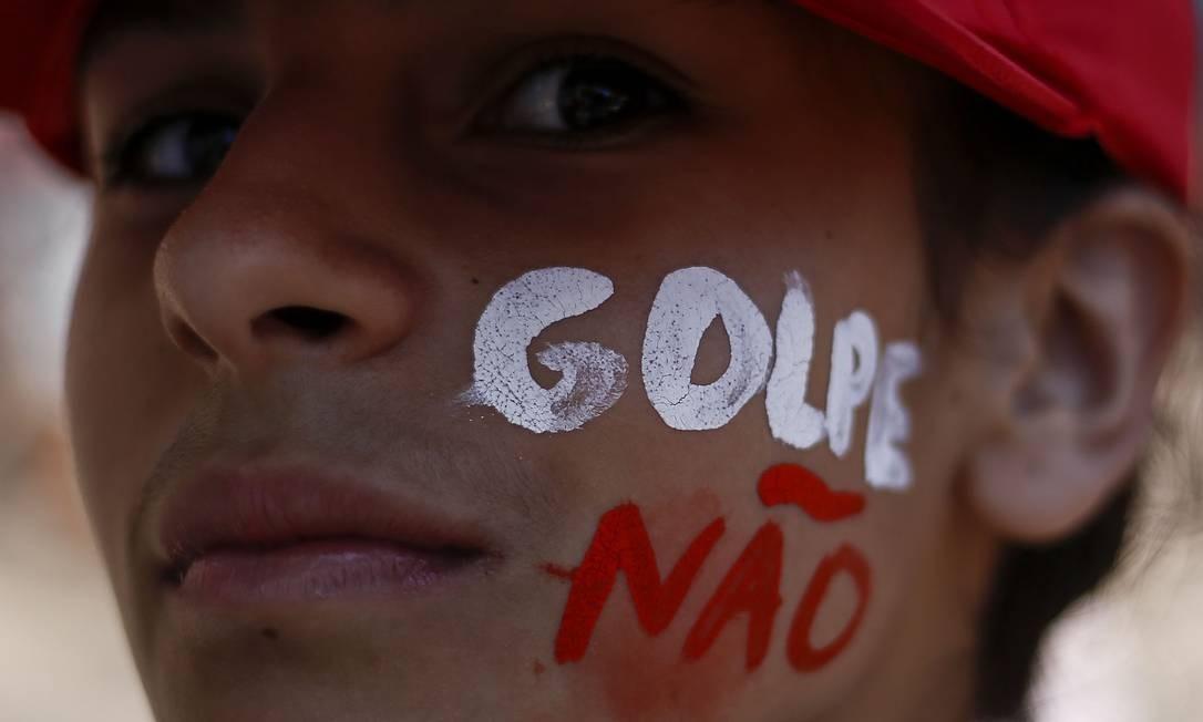 Com tinta no rosto, manifestante protesta contra o impeachment em São Paulo Foto: Miguel Schincariol / AFP