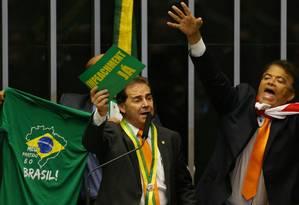"""Deputado Paulinho da Força (SD-SP) exibe placas pedindo o impeachment da presidente. Atrás, uma camisa verde com os dizeres """"Meu Partido é o Brasil"""" Foto: Ailton de Freitas / Agência O Globo"""