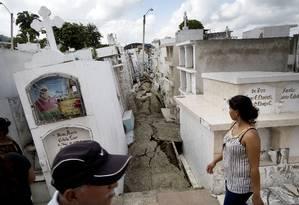 Moradores caminham por cemitério atingido pelo terremoto de 7,8 graus de magnitude que atingiu o Equador no sábado: colapso Foto: Rodrigo Abd / AP