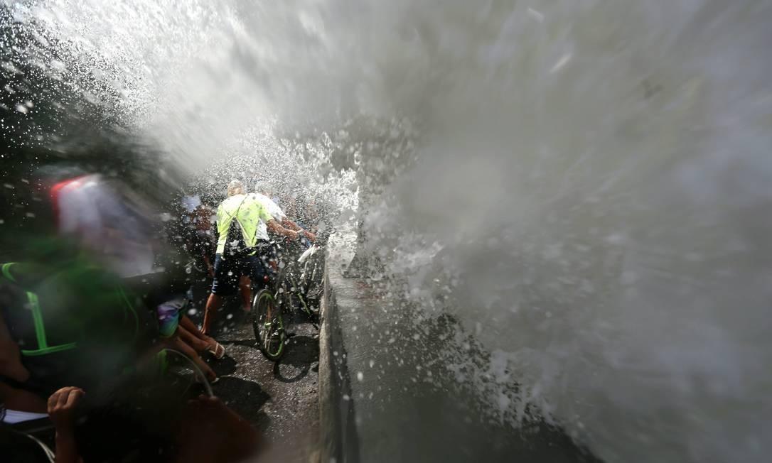 Ciclistas são molhados por onda na ciclovia da Avenida Niemeyer Foto: Custódio Coimbra / O Globo