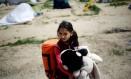 Menina segura brinquedo em acampamento de refugiados na Idomênia, fronteira com a Grécia Foto: STOYAN NENOV / REUTERS