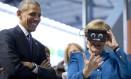 Presidente dos EUA, Barack Obama, sorri ao lado da chanceler alemã, Angela Merkel, que testa óculos de realidade virtual na maior feira do mundo de tecnologia industrial, em Hannover, Norte da Alemanha Foto: Carolyn Kaster / AP