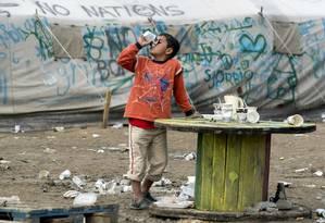 Um menino bebe água em um acampamento improvisado para imigrantes e refugiados perto da aldeia de Idomeni na fronteira entre Grécia e Macedônia Foto: JOE KLAMAR / AFP