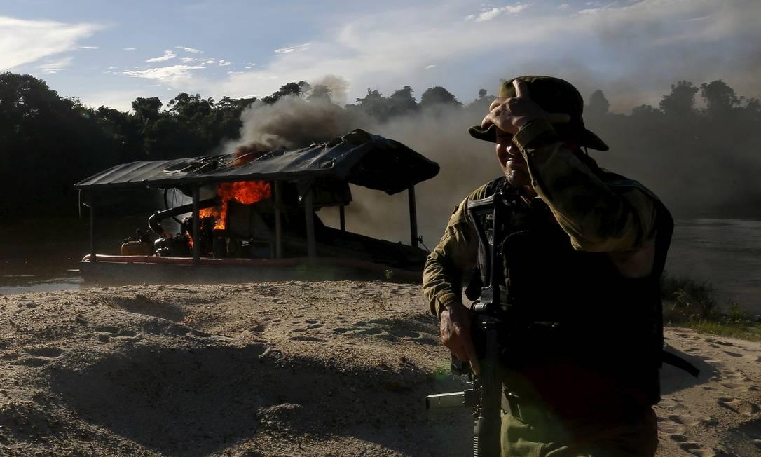 Um agente ambiental acompanha o incêndio de uma draga de ouro perto do Rio Uraricoera, durante uma operação contra o garimpo ilegal no território indígena Yanomami BRUNO KELLY / REUTERS