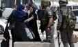 Mulher palestina discute com policial perto do local onde dois palestinos foram mortos por forças israelenses
