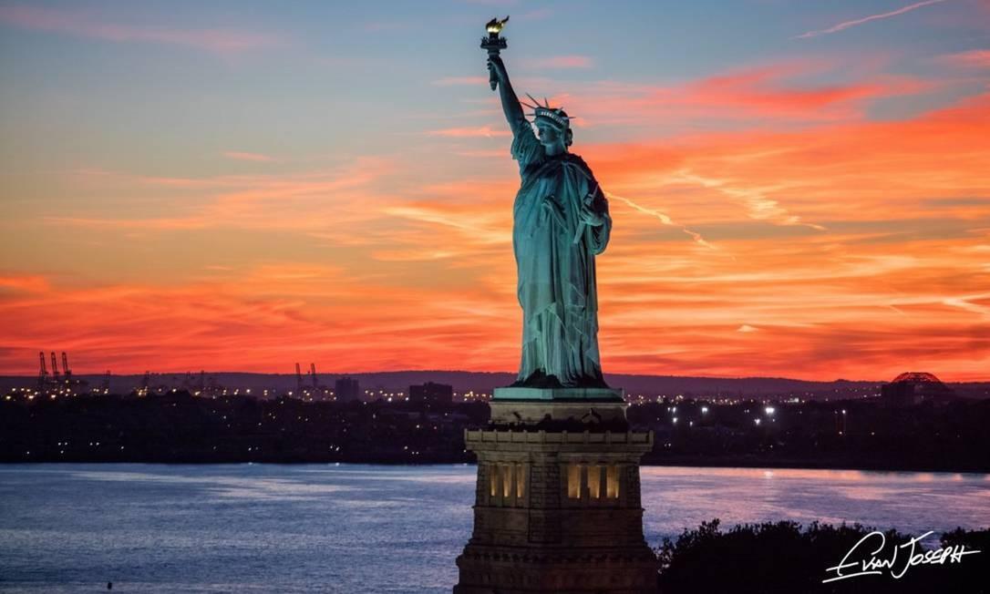 """A Estátua da Liberdade, fotografada no pôr do sol, também faz parte de """"New York from above"""" Foto: Evan Joseph / Reprodução"""