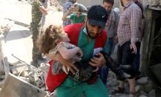 Membro da Defesa Civil carrega uma criança que sobreviveu sob escombros a ataque aéreo em área rebelde de Aleppo Foto: ABDALRHMAN ISMAIL / REUTERS