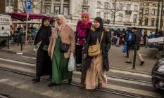 Moradoras usando véu caminham perto de mercado no bairro de Molenbeek, em Bruxelas Foto: DANIEL BEREHULAK / NYT