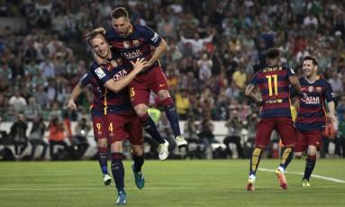 Com Neymar e Messi ao fundo, Rakitic recebe o abraço de Jordi Alba para comemorar o gol da vitória do Barcelona sobre o Bétis Foto: Angel Fernandez / AP