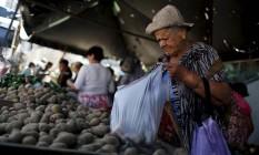 Uma senhora compra batatas em um mercado de rua em Caracas: venezuelanos sofrem com desabastecimento de produtos básicos Foto: CARLOS GARCIA RAWLINS / REUTERS
