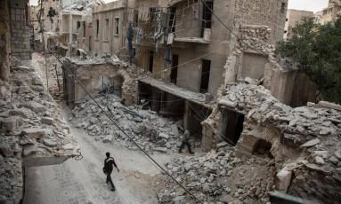 Um homem caminha por prédios destruídos no bairro de Bab al-Hadid, atacado recentemente pelo regime sírio Foto: KARAM AL-MASRI / AFP