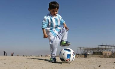 O menino afegão Murtaza Ahmadi com a camisa que ganhou de Lionel Messi: pai da criança diz que família foi forçada a sair de Cabul Foto: Rahmat Gul / AP