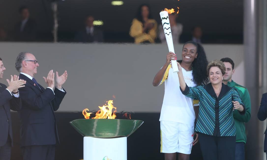 A presidente Dilma Rousseff segura a tocha olímpica com Fabiana, da seleção feminina de vôlei, com aplausos de Carlos Arthur Nuzman, presidente do comitê Rio-2016 Andre Coelho / Agência O Globo