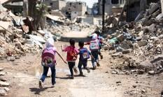 Crianças sírias correm em meio à destruição em Damasco Foto: AMER ALMOHIBANY / AFP