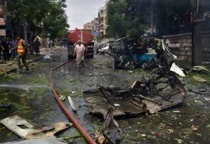 Bombeiros se reúnem em torno de objetos danificados pelo ataque em Aleppo. A foto foi divulgada pela Sana, agência estatal síria Foto: AP
