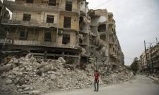 Sírio passa por distrito de Aleppo atingido por bombardeio: MSF acusa potências mundiais Foto: KARAM AL-MASRI / AFP