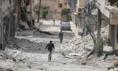 Pessoas caminham entre escombros de prédios destruídos depois de ataque aéreo no distrito Baedeen, em Aleppo Foto: Abdalrhman Ismail / Reuters