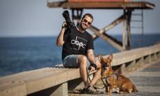 Eduardo Escobar, com o cão Lie, no Quebra-Mar: dupla percorrerá o país de carro Foto: Agência O Globo / Hermes de Paula