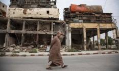 Sírio caminha por ruas destruídas de Aleppo Foto: KARAM AL-MASRI / AFP