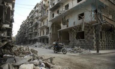 Sírios passam de moto em frente a prédios destruídos na cidade de Aleppo Foto: KARAM AL-MASRI / AFP