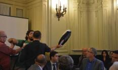 Manifestante joga caixa de pizza na mesa da CPI das Olimpíadas, na Câmara de Vereadores do Rio Foto: O Globo / Luiz Ernesto Magalhães
