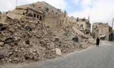 Mulher caminha entre escombros em Aleppo durante confrontos Foto: ABDALRHMAN ISMAIL / REUTERS
