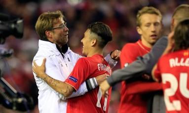 O técnico do Liverpool, Juergen Klopp, dá um abraço especial em Roberto Firmino, destaque do time na classificação para a final da Liga Europa. Após perder a Copa da Liga Inglesa nos pênaltis para o Manchester City, técnico pode ganhar seu primeiro título no clube Foto: Jon Super / AP