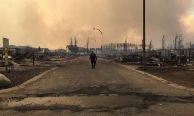 Policial de Alberta caminha em área devastada por incêndio Foto: RCMP / AFP