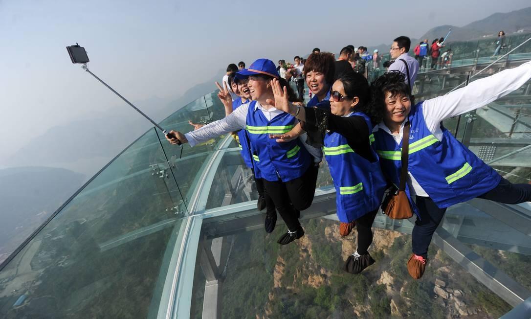 No alto da nova plataforma panorâmica em Shilinxia (China),a diversão é garantida aos turistas, que capricham na pose para a selfie Foto: AFP