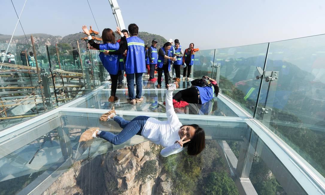 Visitantes não resistem e capricham na pose para aproveitar o visual na plataforma panorâmica recém-inaugurada em Shilinxia, a 100 km de Pequim Foto: AFP
