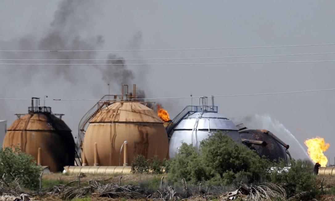 Bombeiros tentam apagar o fogo na refinaria de Taji, 20km ao norte de Bagdá: ataque do EI deixou 11 mortos Foto: AP