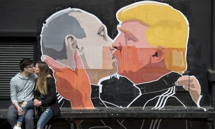 Casal se beija diante do mural com Trump beijando Putin em restaurante da Lituânia Foto: Mindaugas Kulbis / AP