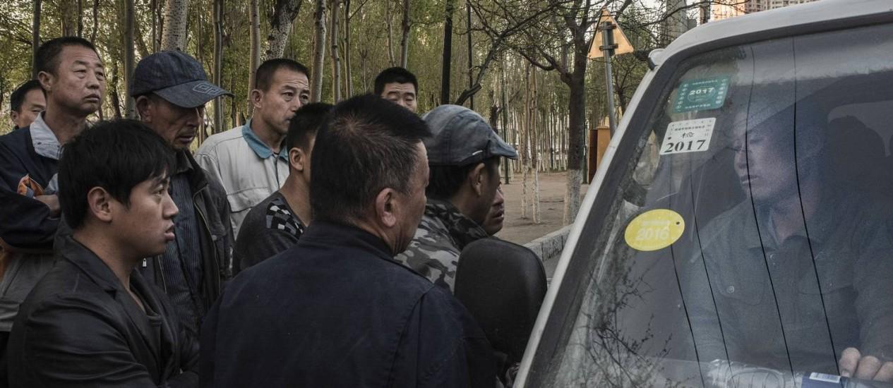 Em Shenyang, cena vai se tornando cada vez mais comum: com crescimento em baixa, desempregados se aglomeram à espera de 'bicos' que vêm em ofertas em cima da hora Foto: GILLES SABRIE / NYT