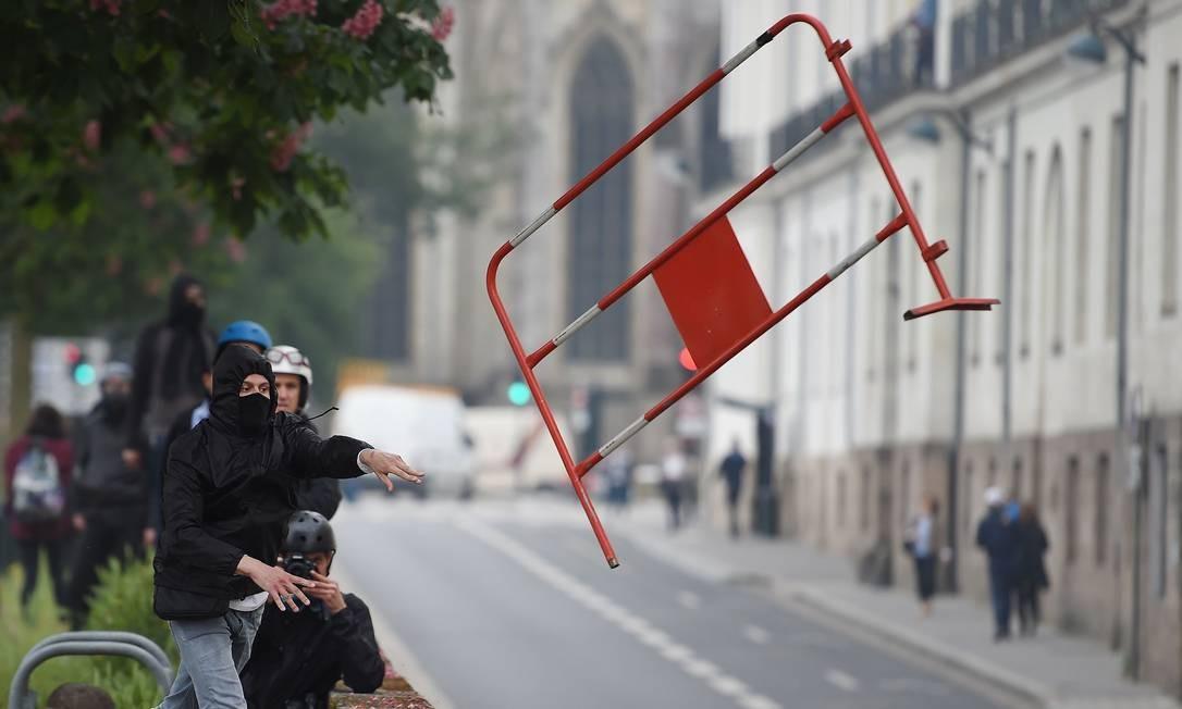 Manifestante atira pedaço de uma cerca em protesto de Nantes Foto: JEAN-SEBASTIEN EVRARD / AFP