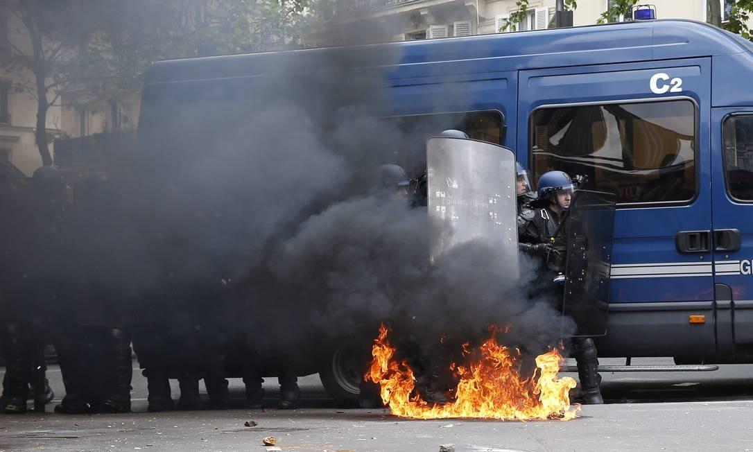 Policiais tentam se proteger de bombas durante confrontos em protestos contra reforma trabalhista de Hollande Foto: THOMAS SAMSON / AFP