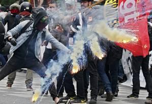 Onda de tensões. Encapuzado solta sinalizador durante manifestação sindical em Paris: com clima tenso, presidente francês é duramente criticado por setores mais à esquerda Foto: GONZALO FUENTES / Gonzalo Fuentes/REUTERS