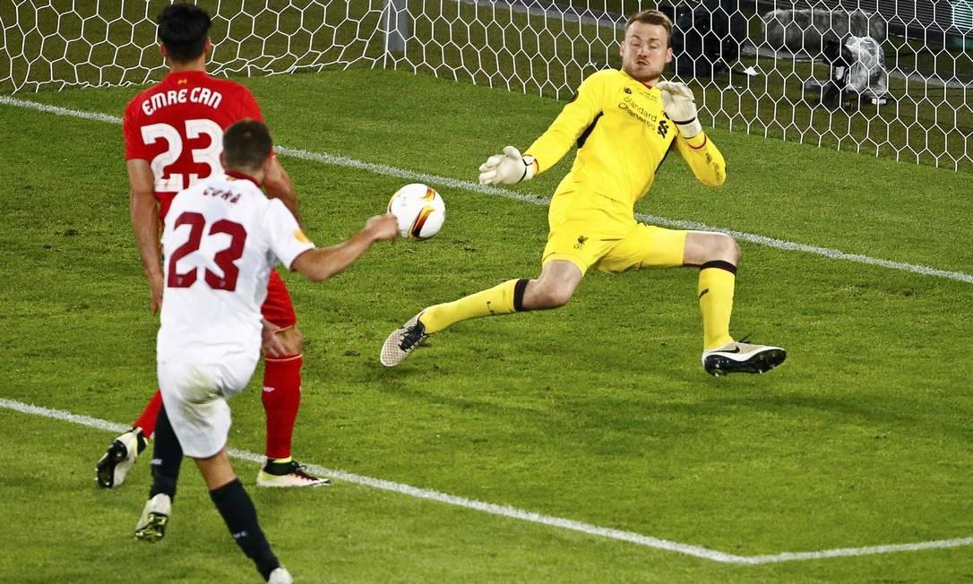 Coke chuta na saída de Mignolet para marcar o terceiro gol do Sevilla Foto: ARND WIEGMANN / REUTERS