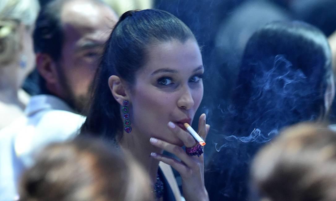 Dentro da festa, Bella foi vista fumando um cigarro em meio aos outros convidados ALBERTO PIZZOLI / AFP