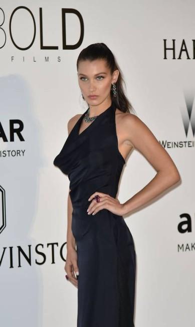 """Depois de """"parar o trânsito"""" com seu vestido cheio de recortes na quinta-feira, Bella Hadid aproveitou a festa da amFAR, em Cannes, com um vestidinho preto mais básico. A top, no entanto, não deixou de se esbaldar dentro do evento ALBERTO PIZZOLI / AFP"""