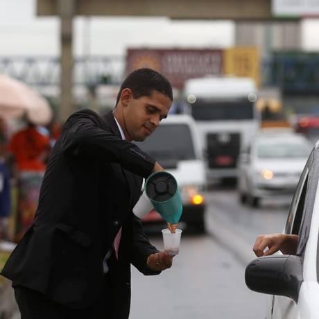 De terno, o pastor Paulo Sérgio serve um motorista na Washington Luís: ele diz que negócio foi inspiração de Deus Foto: Custódio Coimbra / Agência O Globo