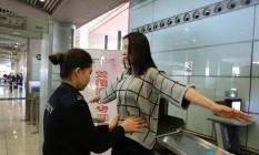 Passageira revistada por oficial do sexo feminino no aeroporto de Pequim Foto: Reprodução / Diário do Povo da China