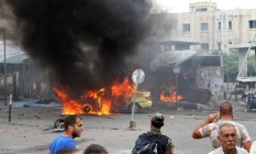 Ataques coordenados. Carro em chamas após explosão de homens-bomba se na cidade costeira de Tartus, na Síria: pelo menos 148 pessoas morreram em nova ofensiva do EI Foto: Uncredited / AP