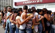 A fila nossa de cada dia. Pessoas se amontoam na entrada de uma farmácia para tentar comprar dois produtos regulados: papel higiênico e fraldas. Muitos delas vão revendê-los Foto: CARLOS GARCIA RAWLINS / REUTERS