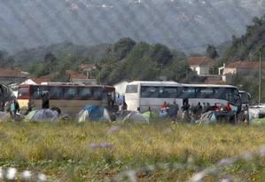 Refugiados e imigrantes embarcam em ônibus para serem transferidos para campos do governo, durante operação para esvaziar acampamento em Idomeni Foto: OGNEN TEOFILOVSKI / REUTERS