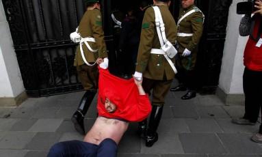Polícia arrasta manifestante em protesto no Palácio de La Moneda em Santiago Foto: STRINGER / REUTERS