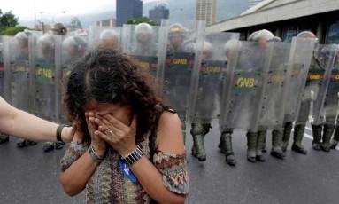 Manifestante chora diante da Guarda Nacional Bolivariana em protesto contra o presidente venezuelano, Nicolás Maduro, no início do mês. Número de mortes causadas por forças de segurança dobrou no país Foto: MARCO BELLO / REUTERS