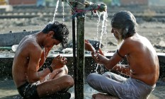 Homens combatem o calor com banho em torneira em Ahmedabad, na Índia Foto: AMIT DAVE / REUTERS