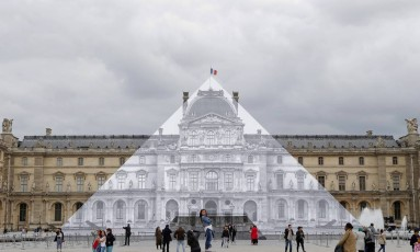 Turistas caminham ao redor da pirâmide do Louvre, envelopada pelo artista plástico JR Foto: Francois Mori / AP
