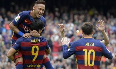Neymar observa Messi enquanto é erguido por Suárez: brasileiro aumentou número de assistências nesta temporada Foto: LLUIS GENE / AFP